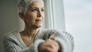 Woman looks out window reflectively