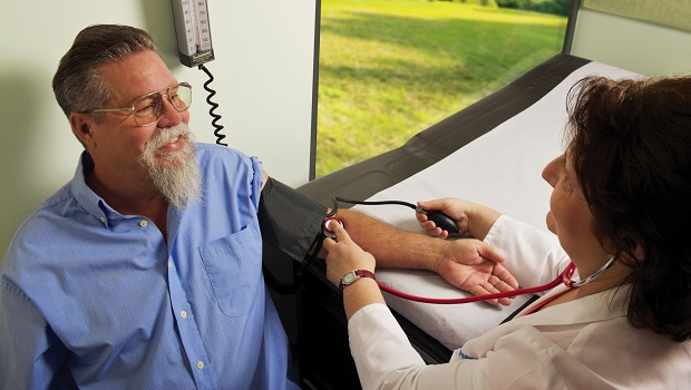 Man sitting down and having his blood pressure taken by a clinician.